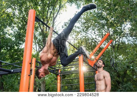 Low-angle view of a shirtless bodybuilder hanging on horizontal bar during extreme calisthenics workout routine in a fitness park with his friend