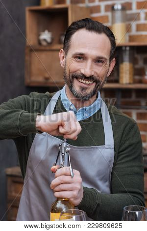 Smiling Man Opening Wine Bottle With Corkscrew And Looking At Camera