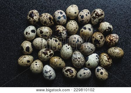 Bunch of raw spotted quail eggs on a black background. Protein source.