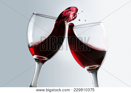 Toasting Of Two Glasses Of Red Wine With Spill