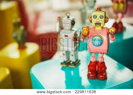 Old Vintage Pink Robot Toy On A Color Blurry Background. Robotics And Design Of The Past.
