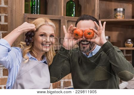 Wife And Husband Having Fun And Grimacing With Pieces Of Vegetable And Fruit