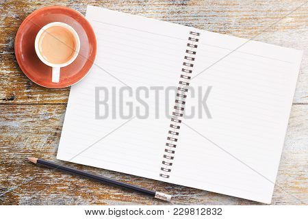 Office Desk Table- Blank Paper Notebook With Pencil And Cup Of Coffee On Wooden Table.view From Abov