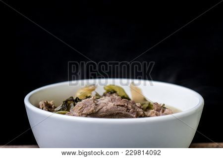 Pickled Lettuce Soup With Spare Rips In White Bowl On Wood And Black Background, Asian Food, Dark To