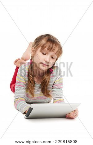 Little Girl Lying On The Floor On Front With Tablet Computer, Over White Background