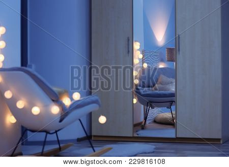 Room interior with wardrobe and stylish rocking chair