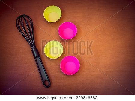 Colorful Cupcake Silicon Baking Cups And Black Whisk Over Wooden Background