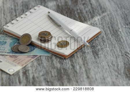 Polish Zloty, Notebook And A Pen On The Wooden Background