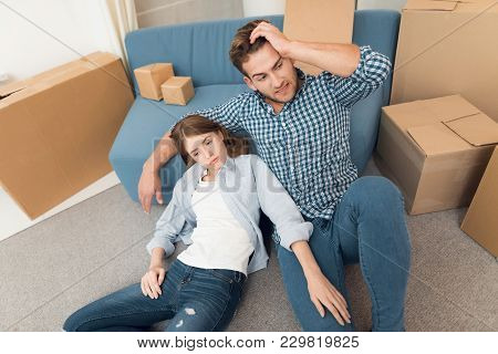 A Young Couple During A Move To A New Apartment. Moving Newlyweds To New Housing. They Sit Among A P