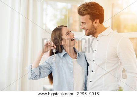 poster of Young couple posing for a photo in a bright room. Newlyweds in the new apartment. The girl holds the key to a new apartment or house. Girl with a guy in a bright room with panoramic windows.