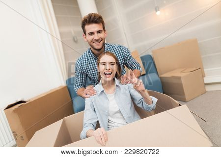 Young Couple Having Fun While Moving To New Apartment. Moving Newlyweds To New Housing. The Girl Is