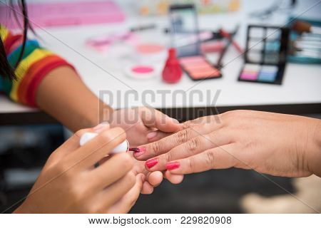 Nail Technicians Are Doing The Nail In The Salon With Cosmetics In The Background.