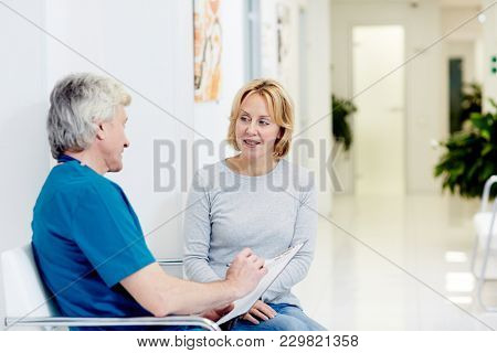 Surgeon talking with woman in corridor at hospital