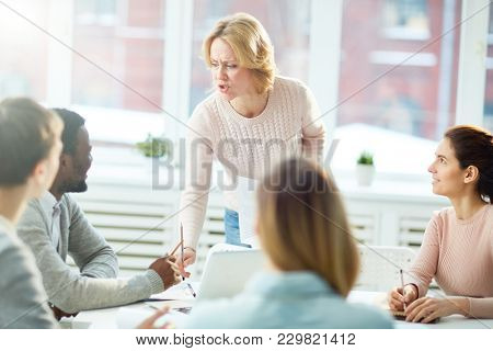 Strict teacher explaining something to young managers at seminar or meeting in office