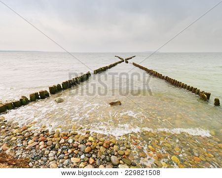 Wooden Breakwaters On A Shore Of The Baltic Sea With A Sun Hidden In Low Clouds. Smooth Water Level