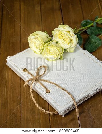 White Roses On Journal Cover With Twine Bow And Rustic Wood