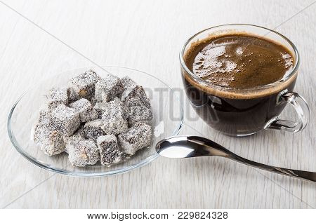 Turkish Delight In Transparent Saucer, Cup Of Black Coffee And Spoon On Wooden Table