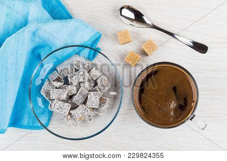 Turkish Delight In Saucer, Black Coffee In Cup, Blue Napkin, Sugar Cubes And Spoon On Wooden Table.