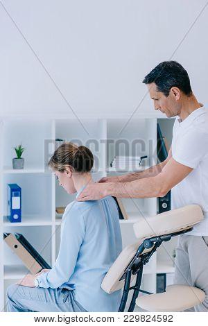 View Of Masseur Massaging Shoulders Of Female Client