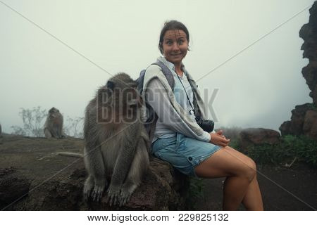 Caucasian Woman In A Shorts Sitting Near Monkey. She Is A Little Afraid Of It. Tourist With Local Fa
