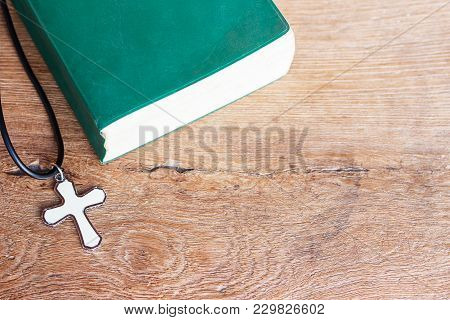 Closeup Christian Cross And Bible On Old Wooden Table With Sunlight. Christian Concept Jesus Is The