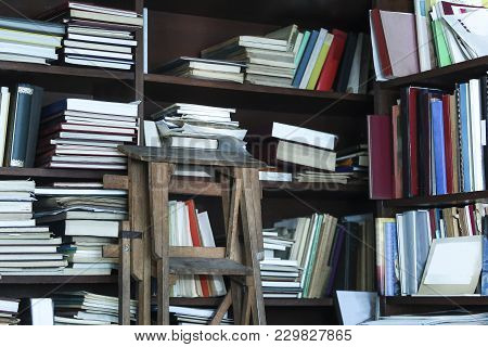 Various Reference Books On Wooden Shelves With Stairs