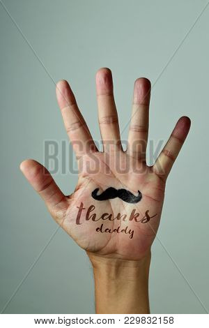 closeup of the palm of the hand of a young caucasian man with a mustache and the text thanks daddy written in it, against an off-white background