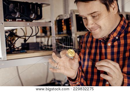 A Man Eagerly Holds A Gold Coin Against The Background Of Computer Equipment. Man Love Money