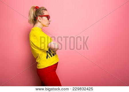 Attractive Woman In Yellow T-shirt, Red Jeans And Sunglasses Standing Sideways With Arms Crossed Iso