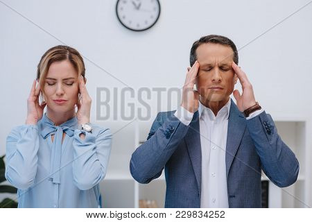 Mature Managers With Headache At Modern Office