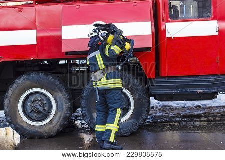A Fireman Standing Near A Red Fire Engine And Holding An Oxygen Balloon In His Hands.