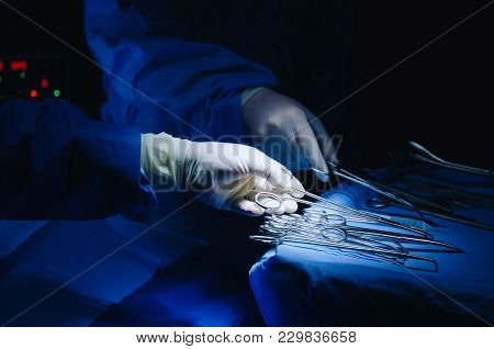 Close Up Surgeons Hand Taking Scissors, Forceps And Surgical Instruments On Table For Operation With