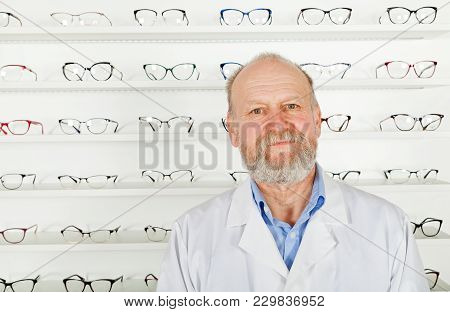 Confident Mature Ophthalmologist Wearing White Uniform In Optical Store