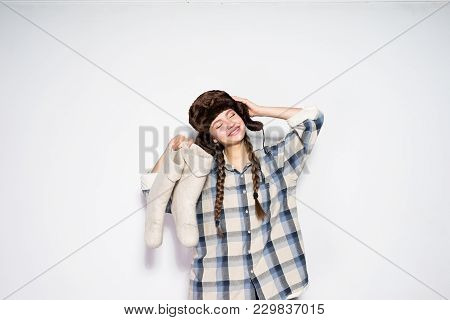 Funny Happy Girl From Russia In A Warm Fur Hat Holds Warm Gray Felt Boots