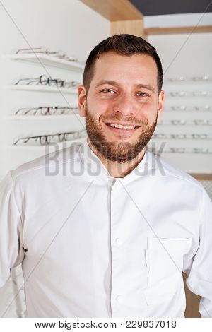 Portrait Of Young Ophthalmologist Wearing White Coat, Smiling At The Camera In Optical Store