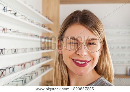 Seductive Young Woman Choosing Eyeglass Frame In An Optical Store, Winking At The Camera