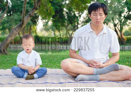 Father With Eyes Closed And Cute Little Asian 18 Months / 1 Year Old Toddler Baby Boy Child Practice
