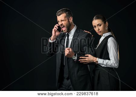 Angry Boss Yelling While Talking On Smartphone, Businesswoman Standing Near, Isolated On Black