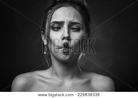 Fun Girl On Black Background Looking At Nose Making Grimace With Her Lips, Monochrome