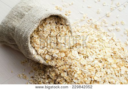 Rolled Oats Scattered From Burlap Bag On White Wooden Table Background