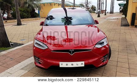 Menton, France - March 3, 2018: Red Tesla Model X Electric Car Parked On A Square In Menton On The F