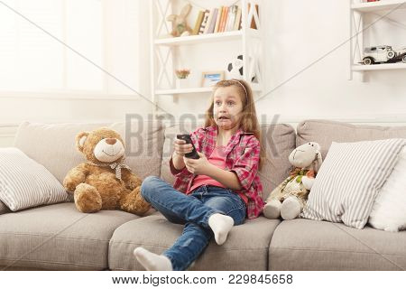 Confused Little Casual Girl Watching Tv At Home. Female Kid Sitting On Sofa With Her Toy Friend Tedd