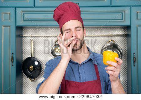 Chef Show Ok Gesture To Sweet Pepper. Cook Man In Red Hat, Apron Taste Vegetable In Kitchen. Vegetar
