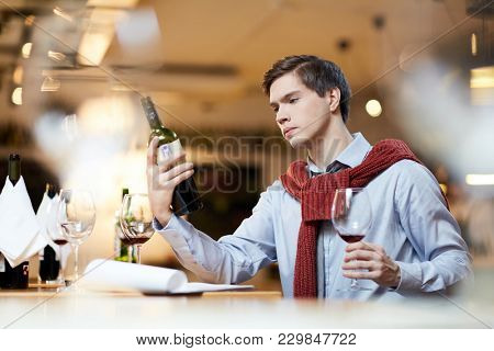 Sommelier holding bottle of wine and testing red wine at restaurant