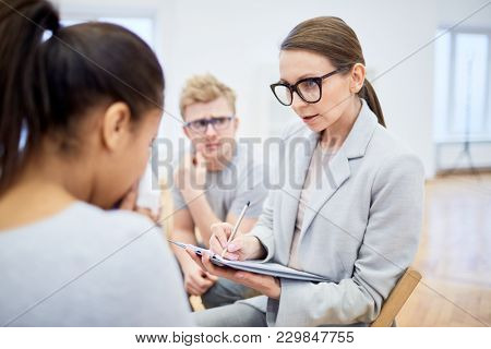 Confident psychologist in formalwear and eyeglasses consulting young woman and making notes during session