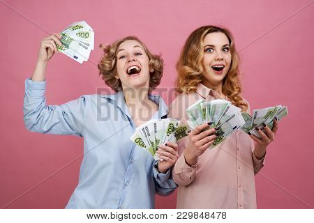 Portrait Of Two Young European Girls With Cash Euro In Hand And Happy Joyful Expression. They Are De