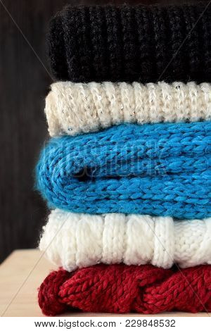 Knitted Scarves Of Different Colours Are Piled Carefully