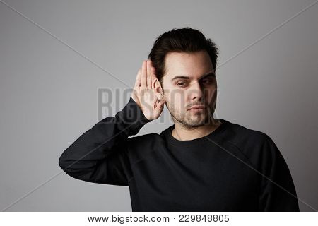 Portrait Of Young Casual Man Which Overhears Conversation Over White Background.