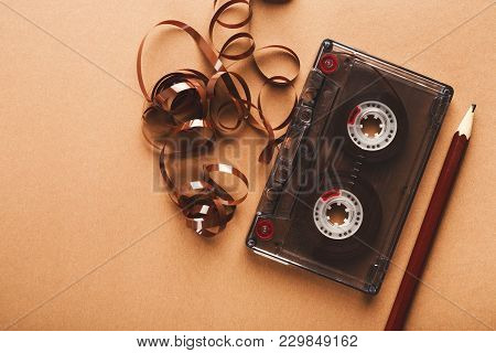 Retro Audio Cassette And Pencil On Light Brown Background. Top View On Vintage Tape And Simple Devic