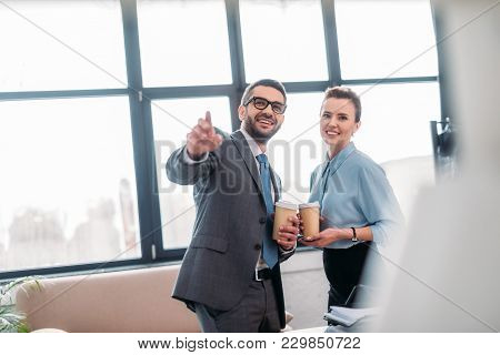 Businesspeople Having Coffee To Go At Office And Pointing Somewhere